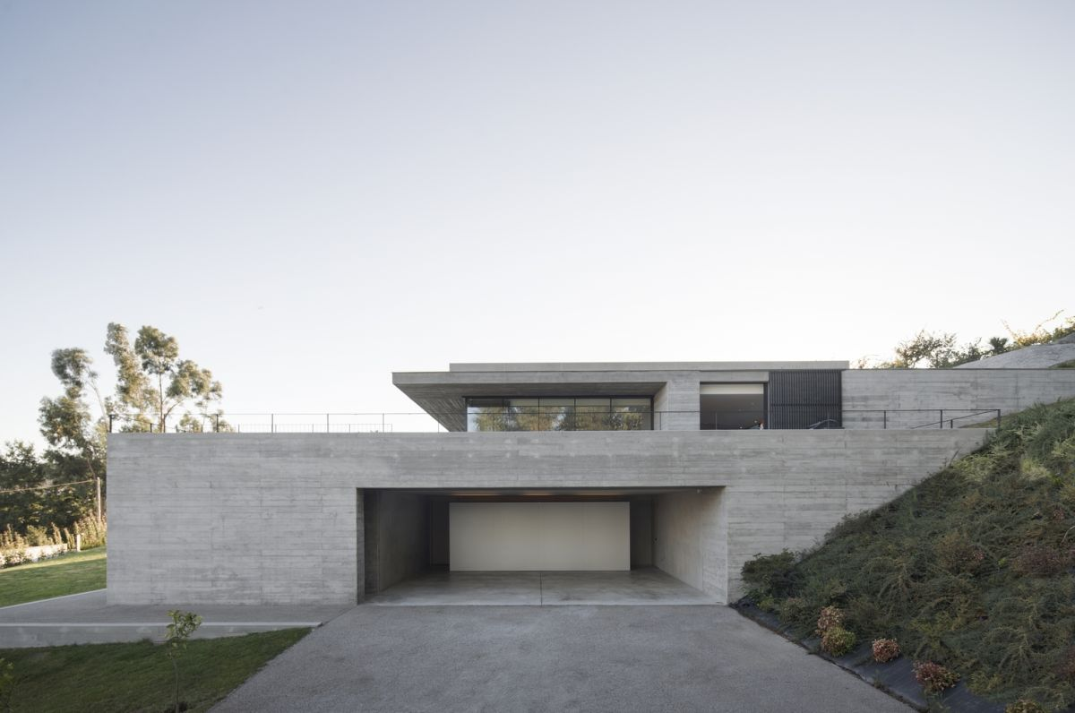 The sections of the house that are not integrated with the land reveal a minimalistic, light gray exterior