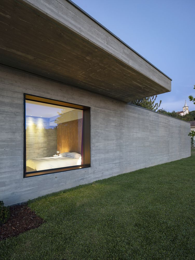 The oversized floor of the upper level creates overhangs for some of the ground floor spaces