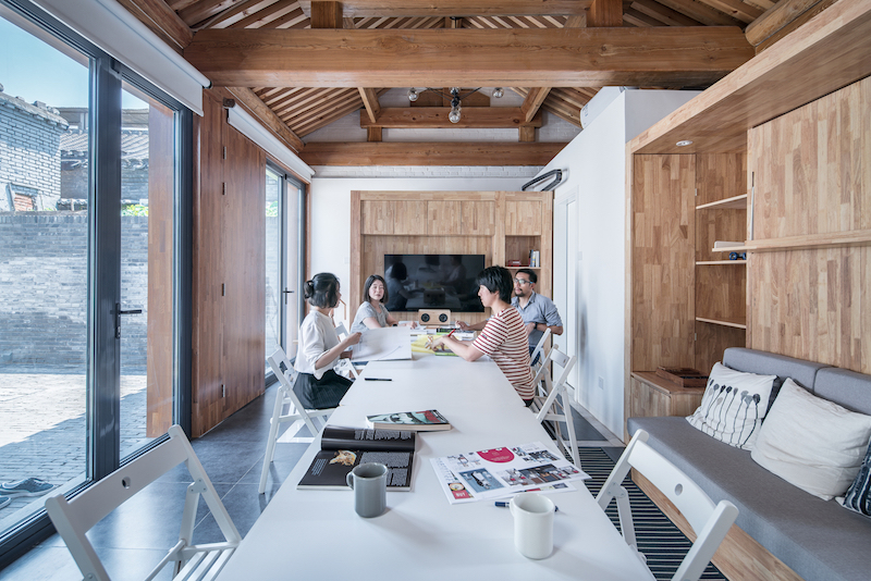 In one of the configurations, a large dining table sits at the center of the living area