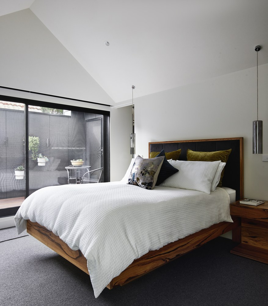 Upstairs there's a bedroom with a stylish and simple interior and access to an open balcony-like space