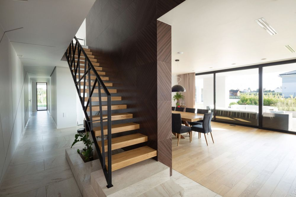 The staircase which connects the two floors is partially hidden behind an accent wall