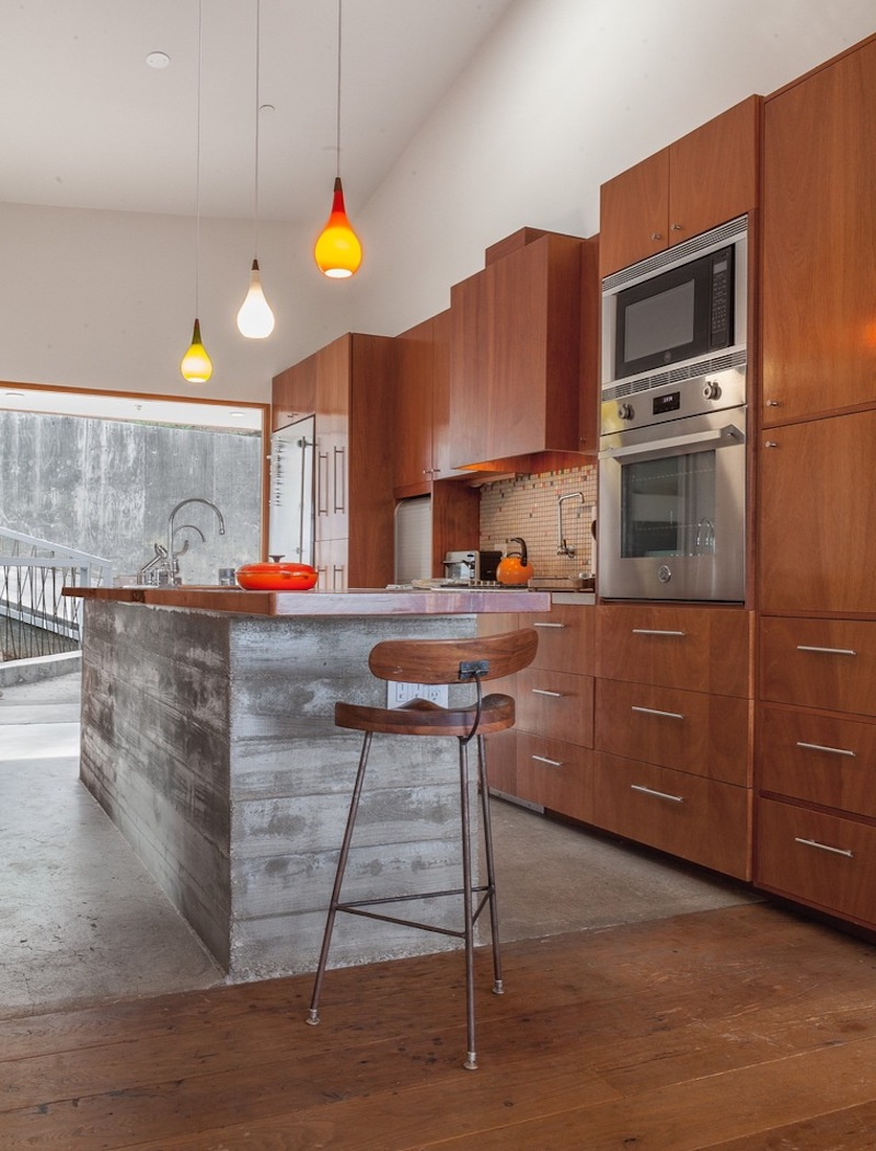 The kitchen features a lovely island which seems to be built using reclaimed wood