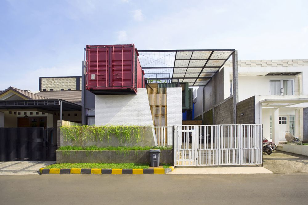 Four shipping containers of different colors have been incorporated all throughout this beautiful family home