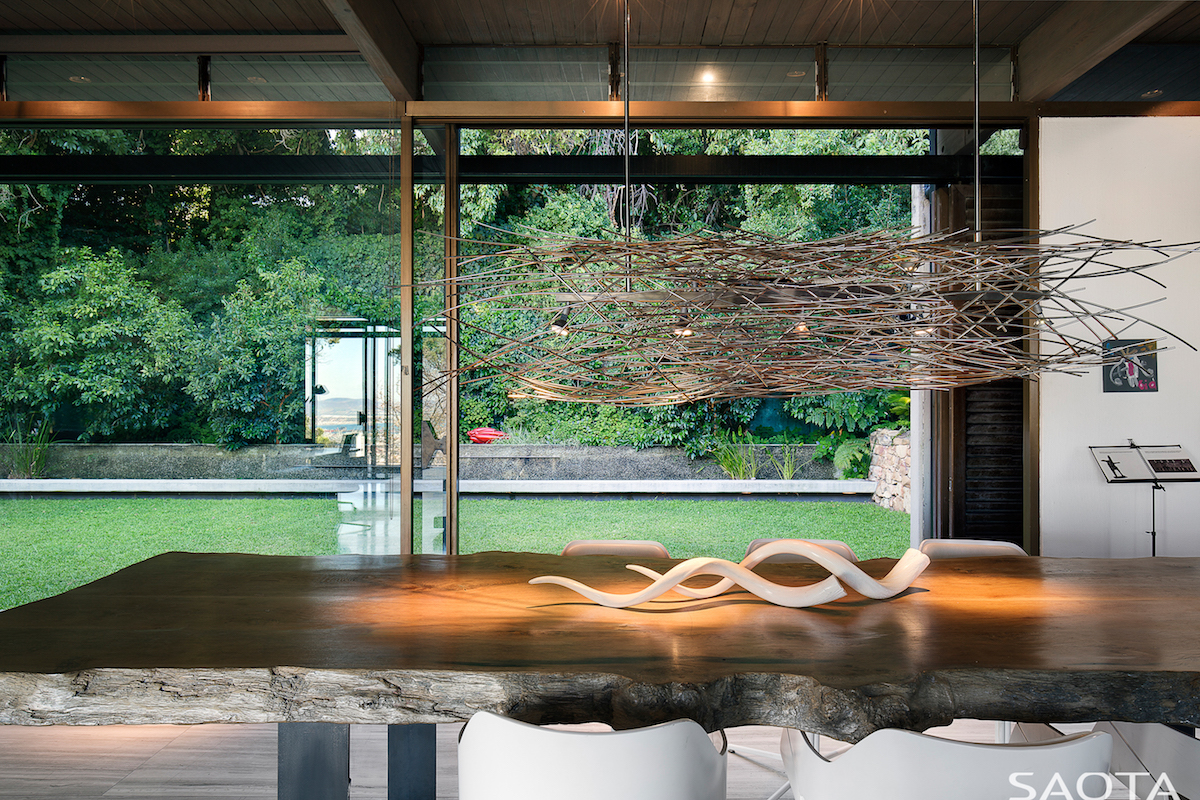 The dining area has a live-edge table with a gorgeous chandelier above it