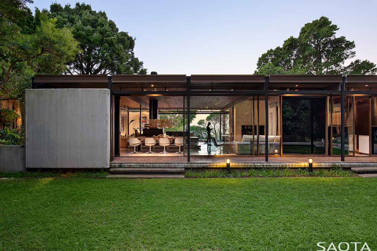 The backyard has a manicured lawn which frames the house on one side