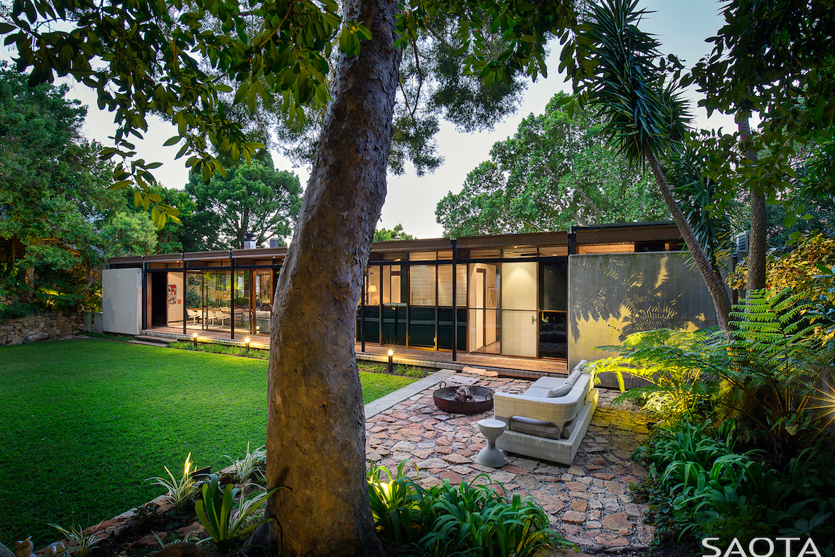 A lovely outdoor lounge space flanks the lawn, featuring a stone floor pierced by greenery