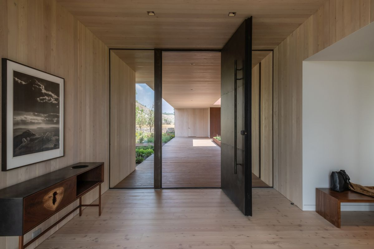 A large pivoting front door marks the entrance to the main house