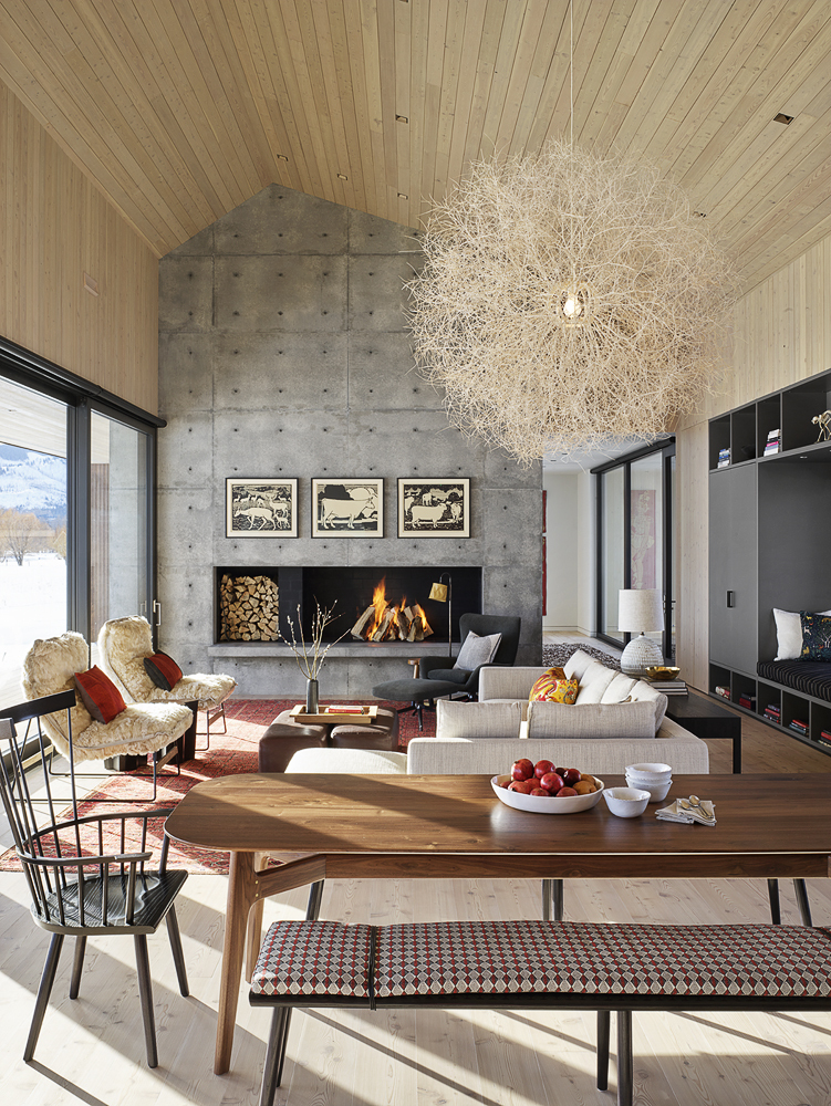 The living area has a large concrete fireplace which puts an emphasis on the asymmetrical shape of the roof