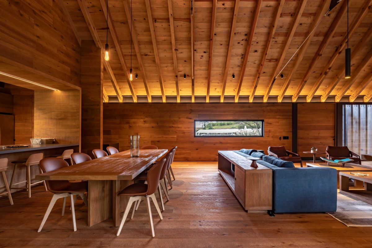 The kitchen, dining area and living room are combined into a single large space wrapped in wood