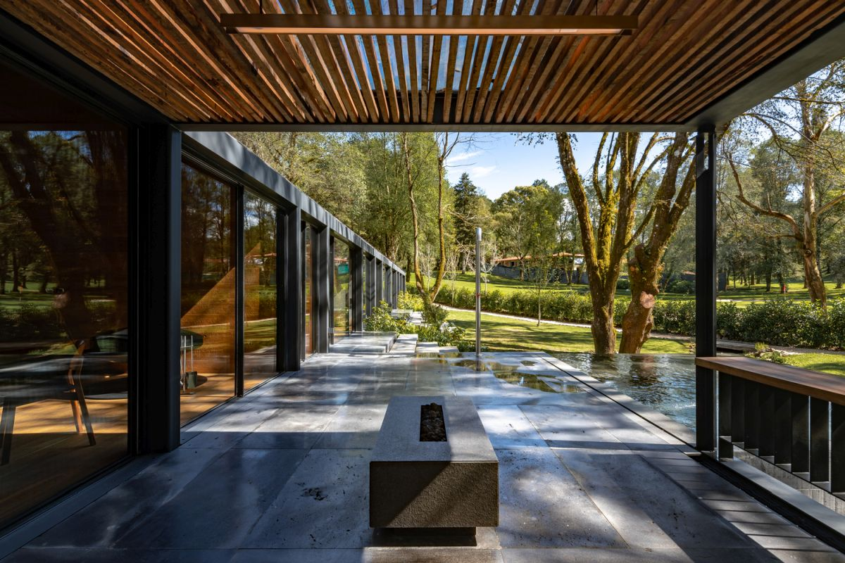 A large patio with a pergola roof and a fire pit extends the living areas outside