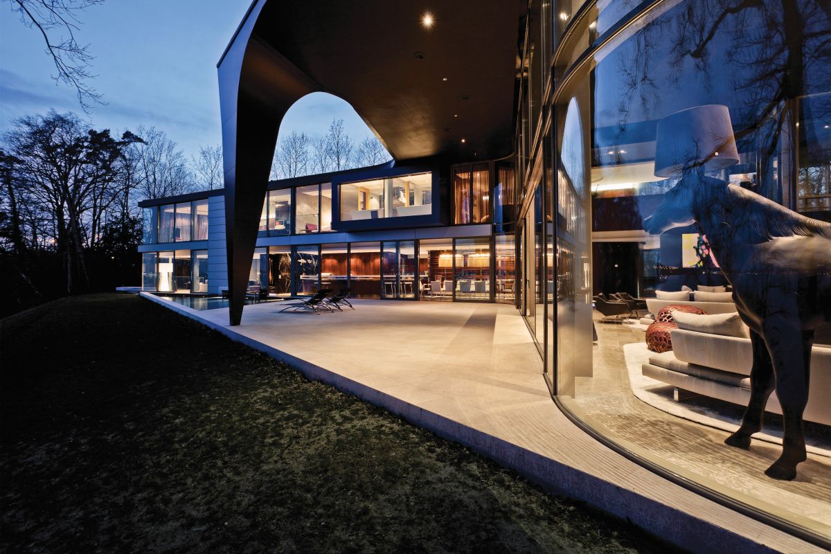 A curved glass wall defines the large living area and frames the gorgeous view over the lake
