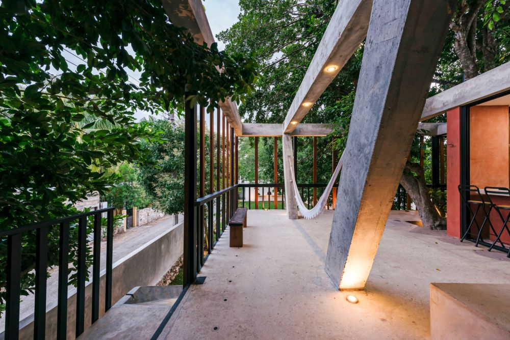 The support pillars extend through the concrete floor and transform into a hammock stand for this terrace