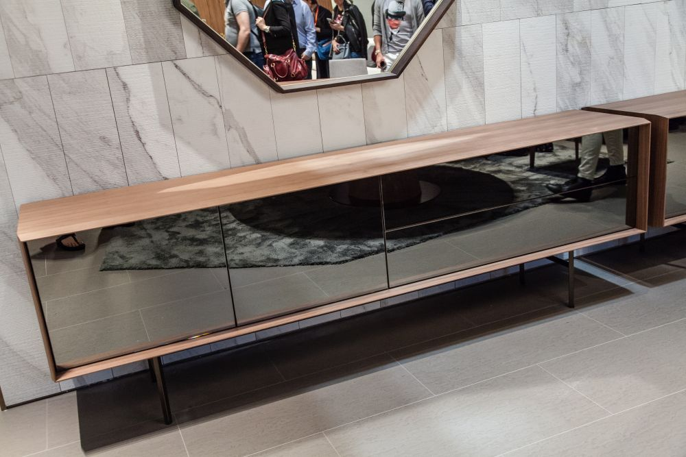 A media unit or a low cabinet with mirrored front panels is able to reflect the floor and rug