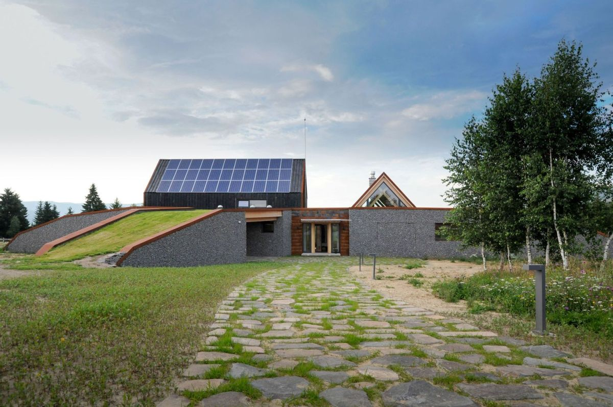The south-facing side of the roof is entirely covered in photovoltaic panels