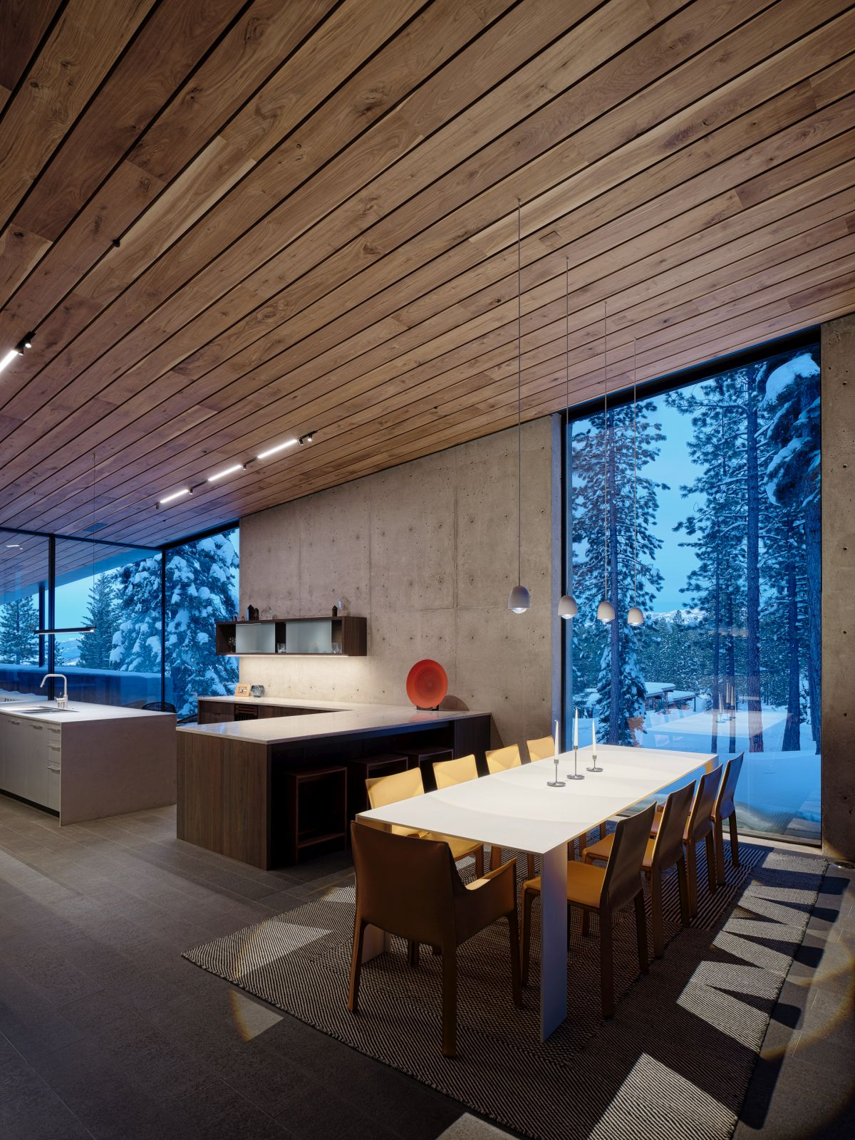 The kitchen and dining area share a large open space with a wooden ceiling, concrete walls and full height windows
