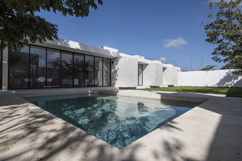 The back yard features a square-shaped swimming pool framed with concrete decks