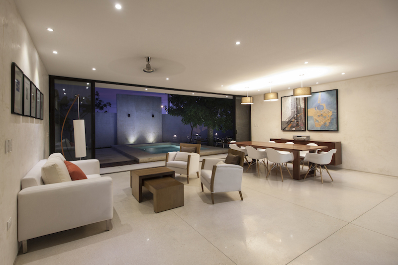The social areas has large floor tiles, white walls with a textured finish and minimalist lighting