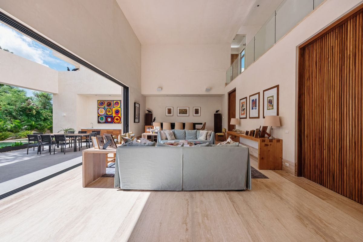 The central volume of the house has a high ceiling and large sliding doors facing the terrace and garden