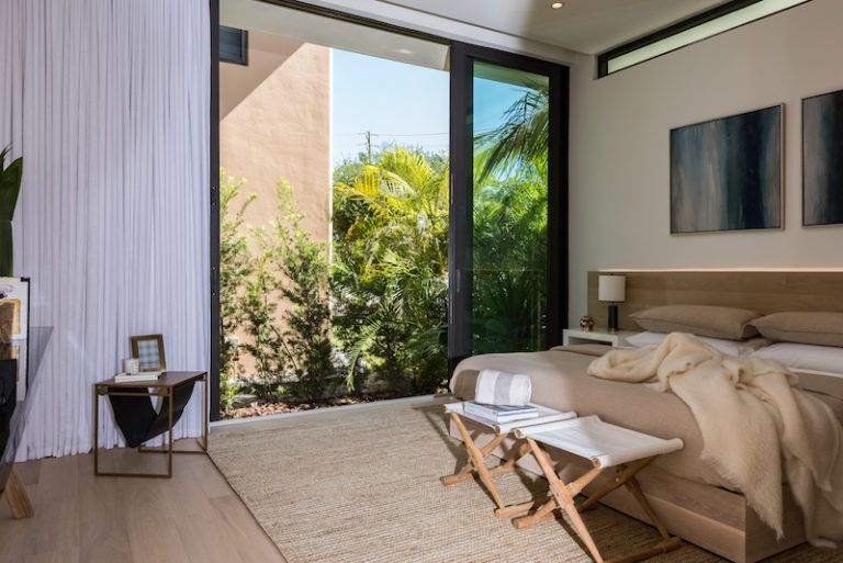 The glass doors bring in natural light and freshness while the greenery provides privacy