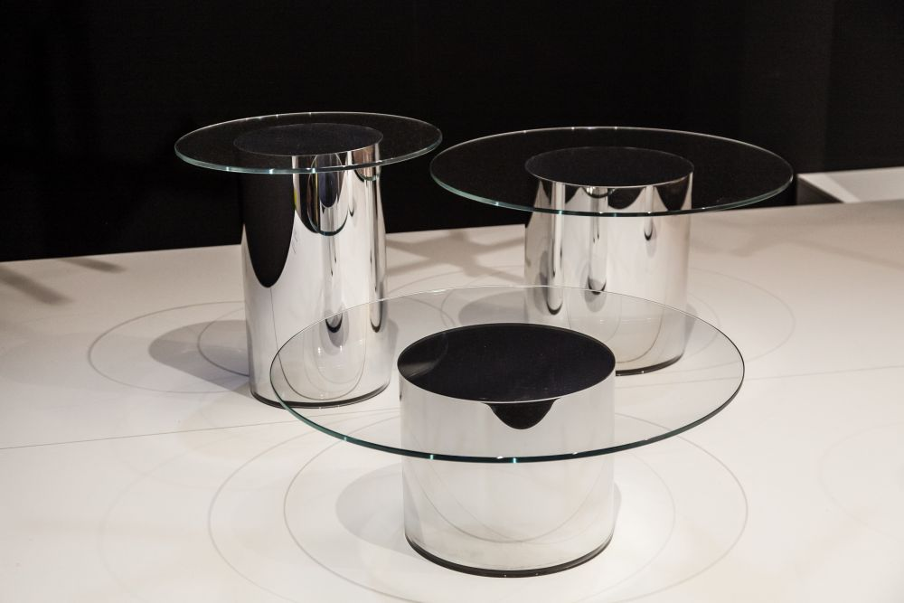 The tables in this series have no visible joints, featuring round glass tops placed on metal cylinders