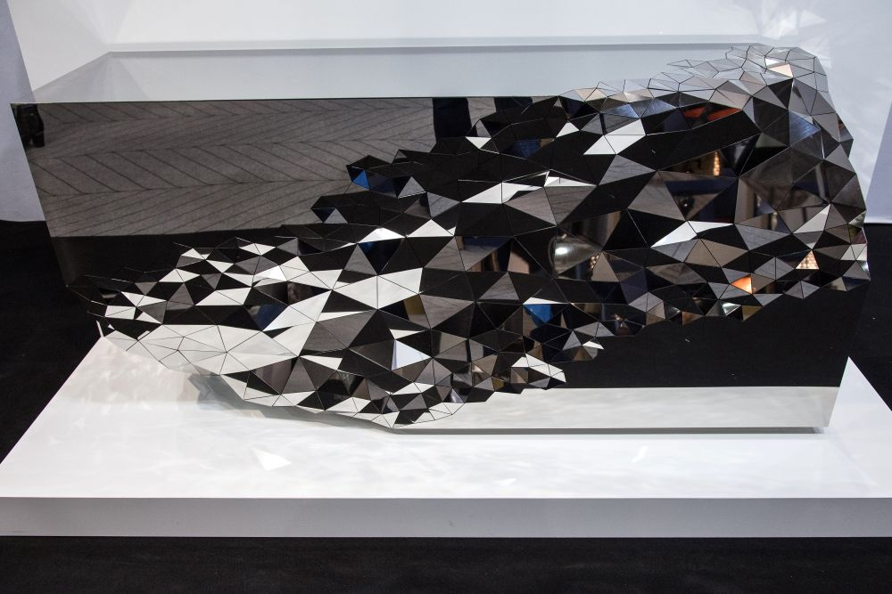 The sculptural nature of this console's design emphasizes its glamorous look, being reminiscent of diamonds