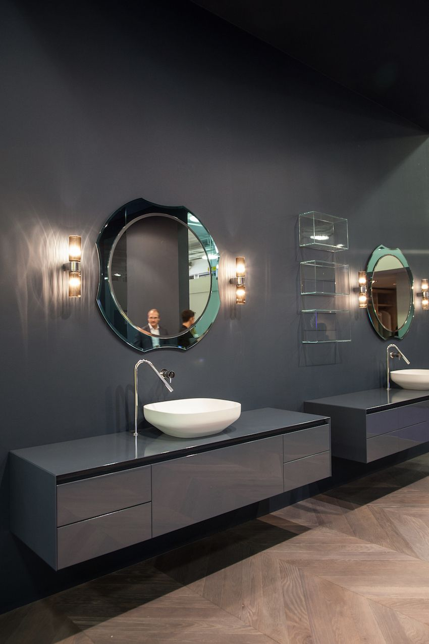 Decor details like a more opulent light fixture and a mirror that has curved lines softens the look of angular modern bathroom fixtures.