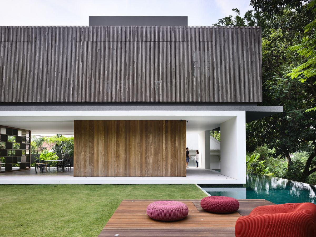 The house has a large backyard with a swimming pool, a wooden deck and lots of greenery