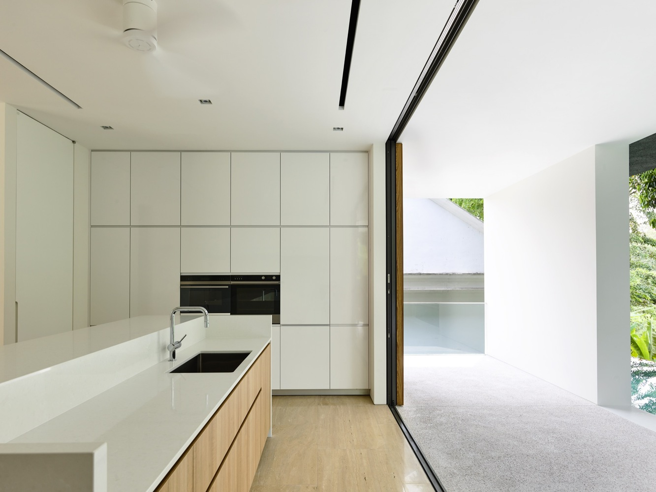 Sliding doors ensure a seamless connection between the kitchen and the outdoor spaces