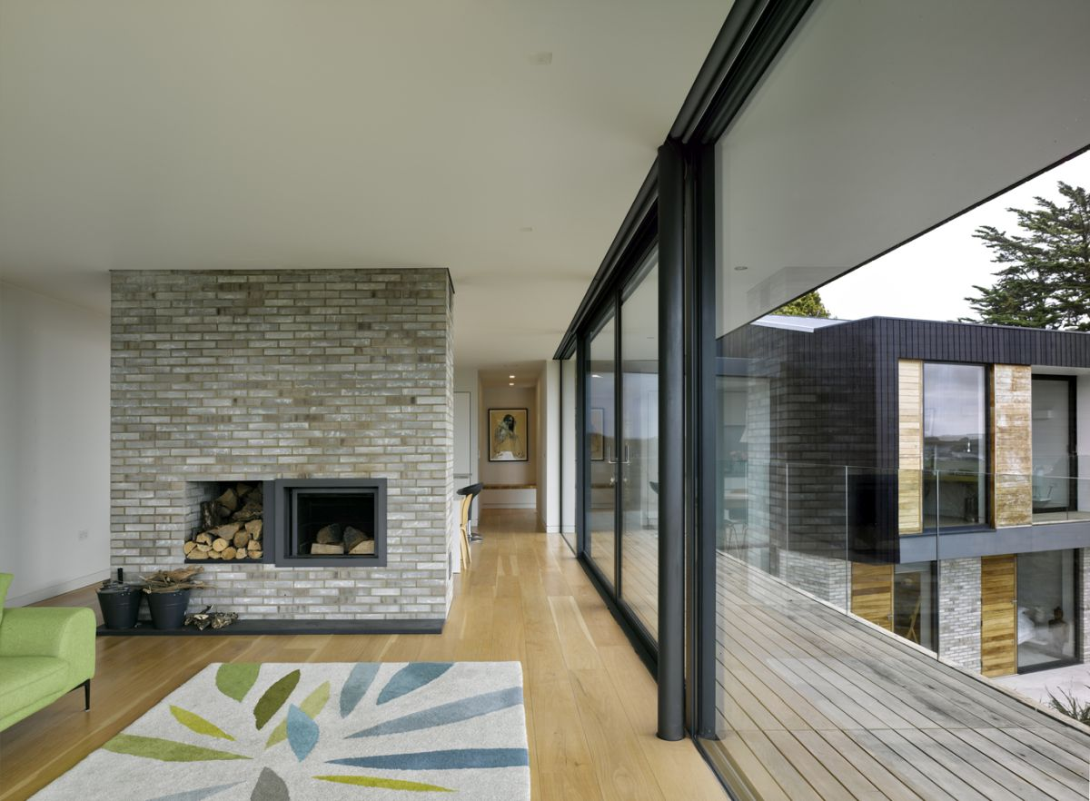 The living room has a fireplace which doubles as a space divider, separating the lounge area from the rest of the floor plan