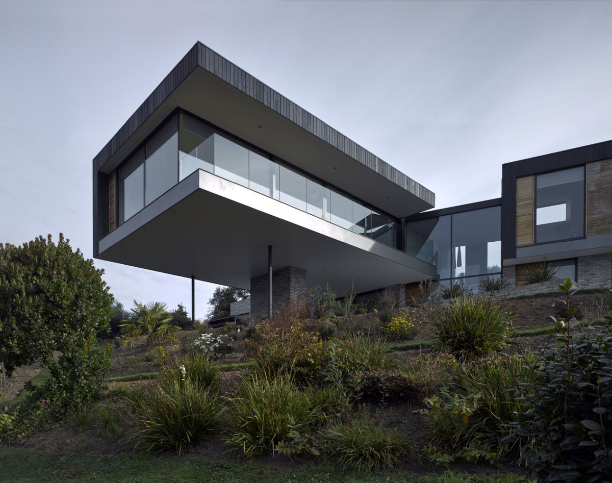 The cantilevered section of the house forms a protective roof over ground floor deck