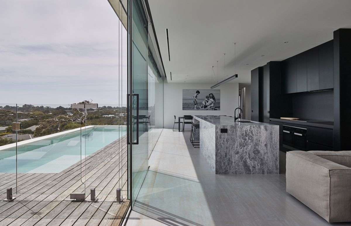 The living room and kitchen overlook the pool deck and have a glazed facade
