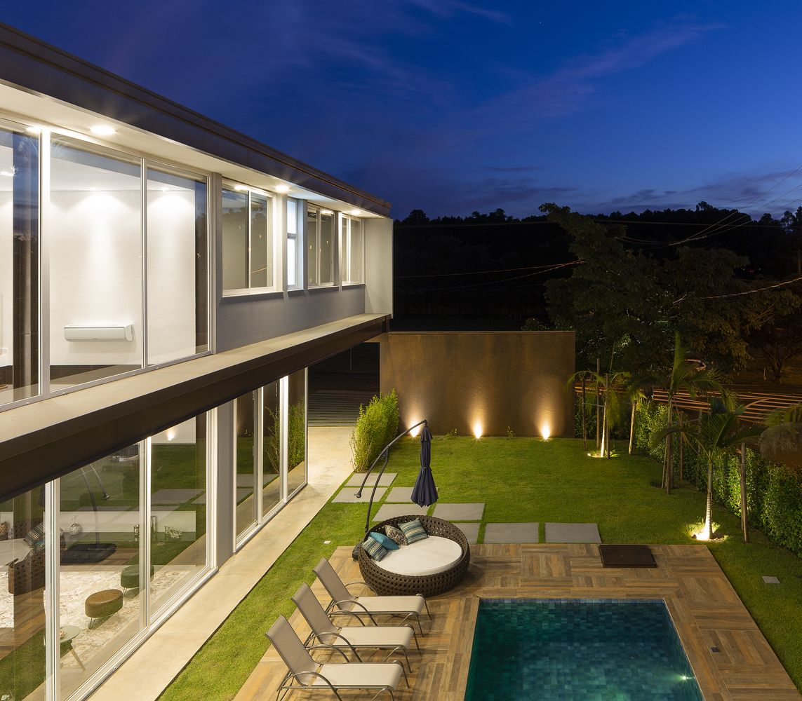 The backyard has a swimming pool which is elegantly framed by a wooden deck