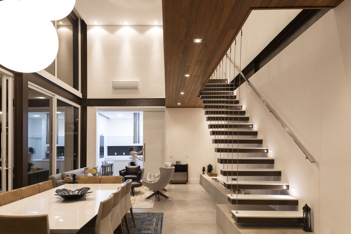A floating staircase with cord railing connects the two floors without blocking the views