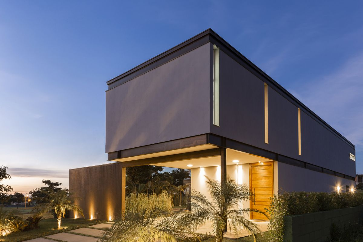 The tall wooden doors contrast with the metal frame and concrete exterior