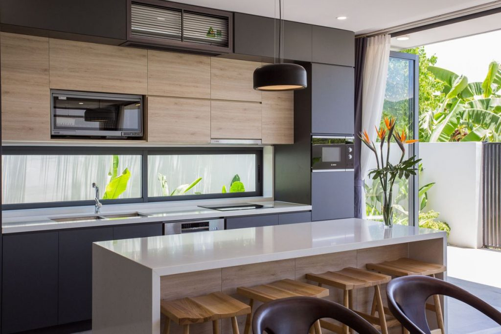 The kitchen has easy access to a small garden and features long and narrow windows instead of a typical backsplash