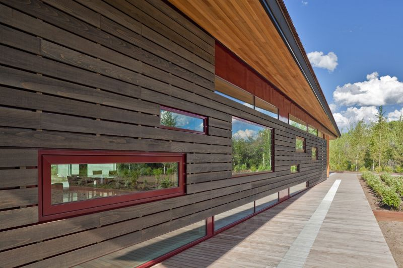 Windows of various shaped and sizes pierce the wooden wall letting the light and the views in