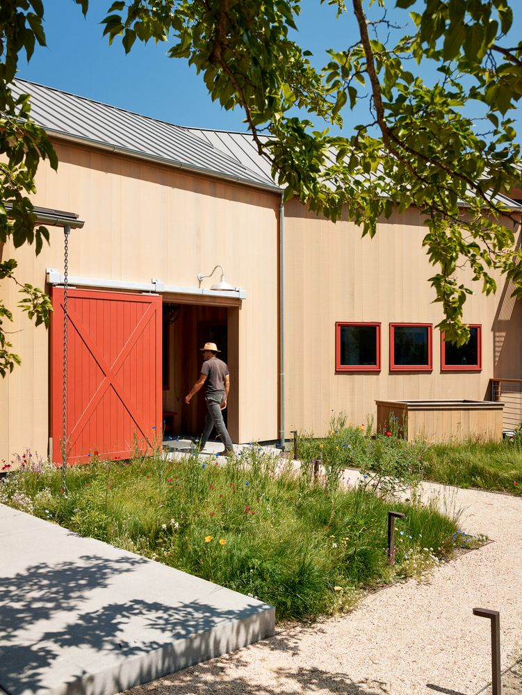 The pavilion has large red doors that highlight its barn-like rustic beauty