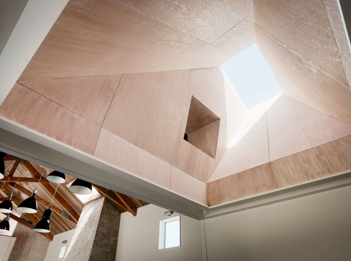 A double-height skylight shaft brings light from above into the open space kitchen