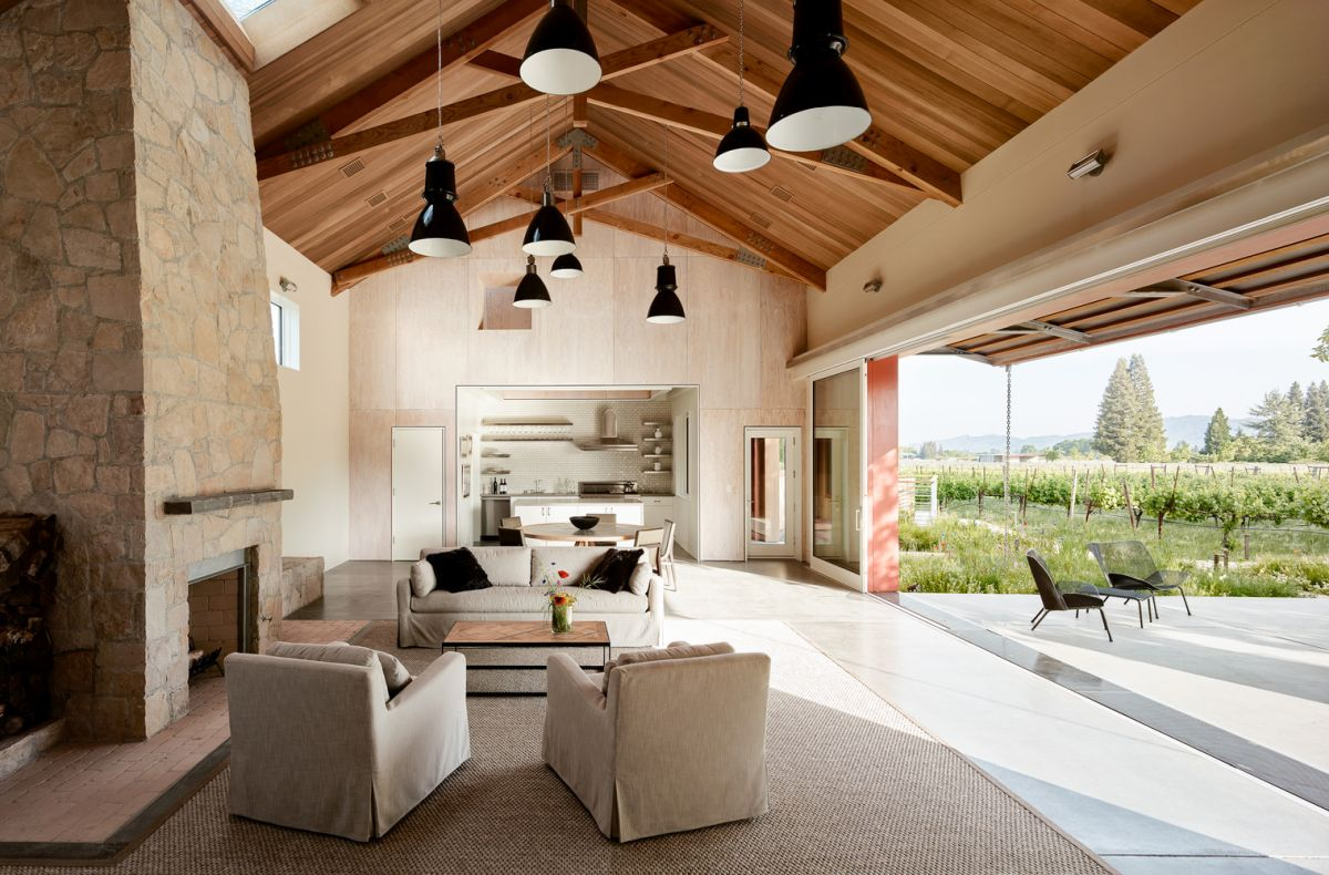 The central living area is a double-height space with a fireplace built out of local stone