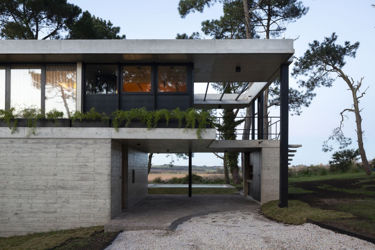 The upper floor is partially cantilevered over the concrete base which gives it a lightweight appearance