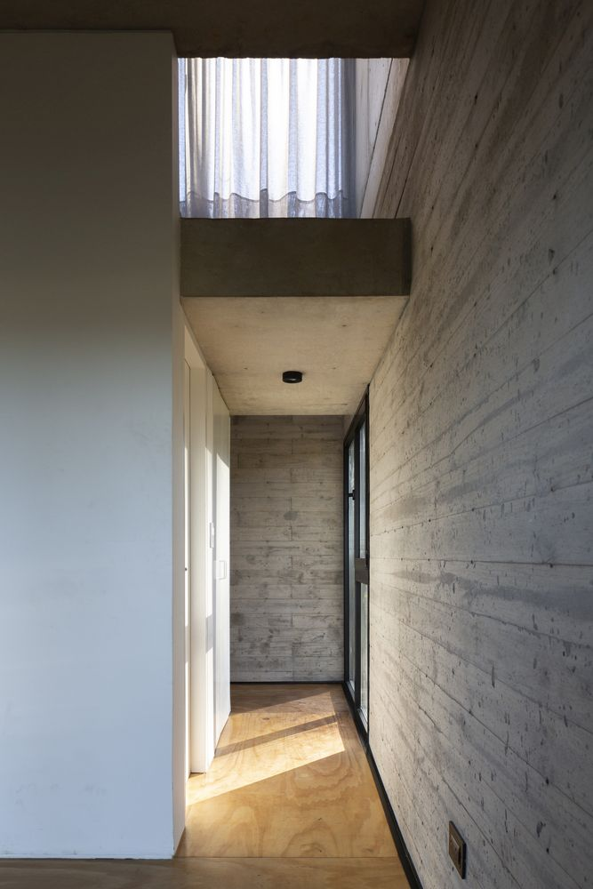Raw concrete walls are complemented by wooden floors for a balanced and modern look