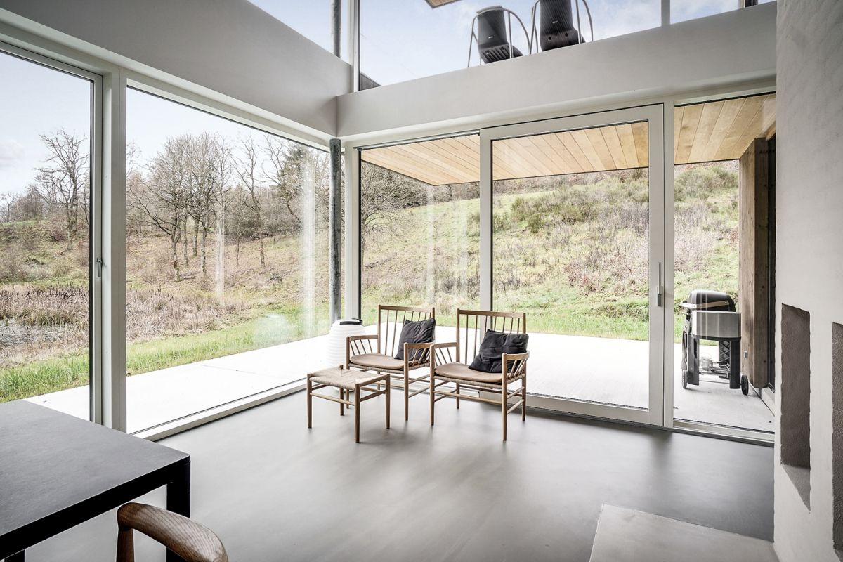 The dining area is a double-height space with huge windows and a connection to the covered deck