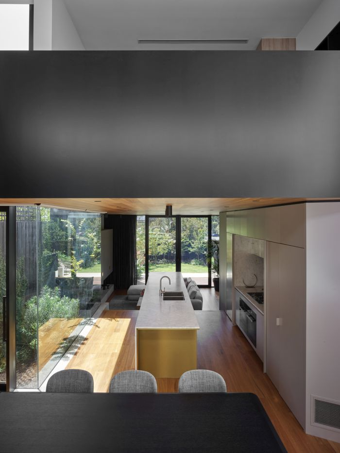 Full-height windows fill the kitchen with natural sunlight during the day