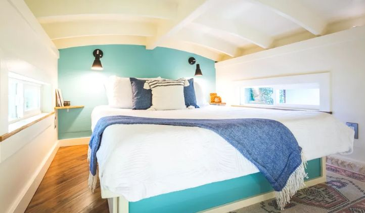 The loft bedroom has a curved ceiling with exposed beams and two elongated windows on opposite walls