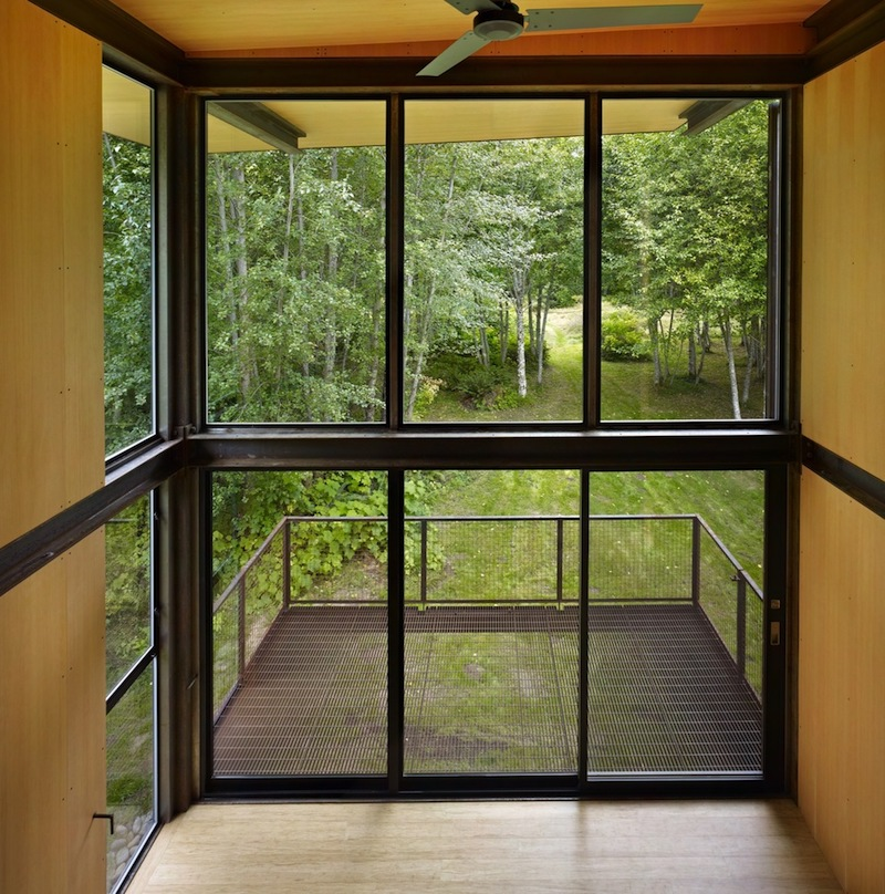 A glazed facade opens onto a small deck suspended above the ground, with views of the trees