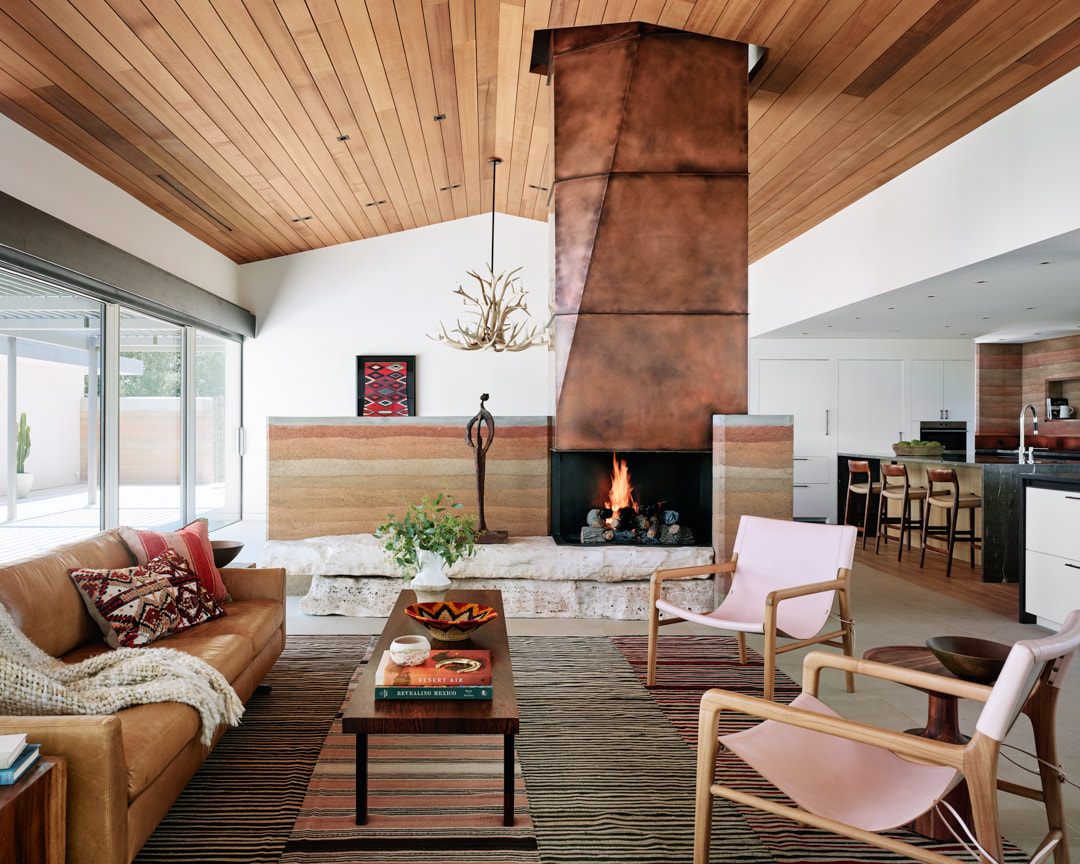 Indoors the main seating area has a big weathered metal fireplace as a focal point