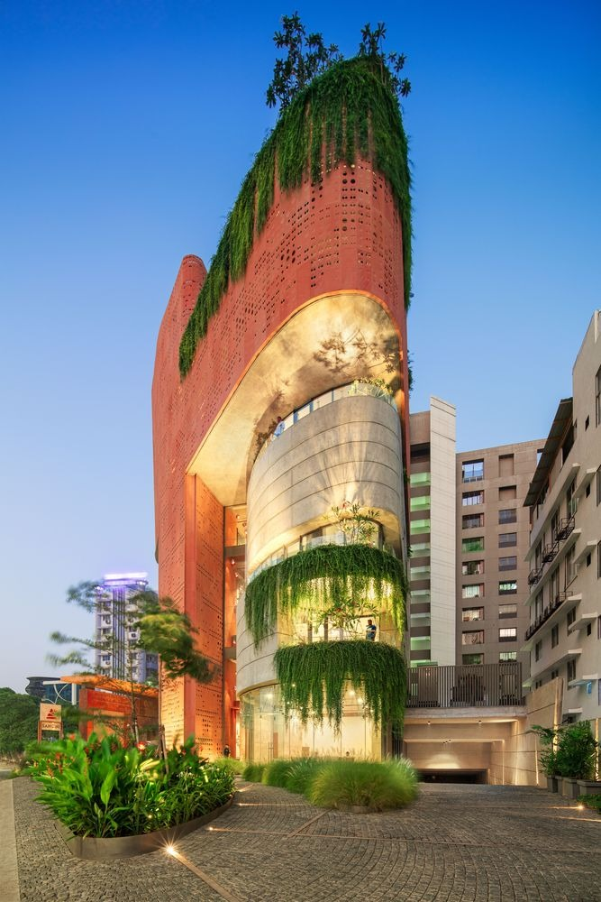 The perforated facade has a beautiful brick0inspired color which contrasts with the concrete and the glass