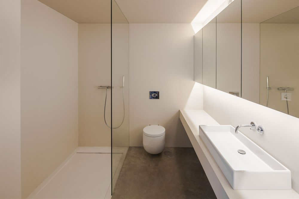 The bathroom features a minimalist design and big mirrors which make it seem larger