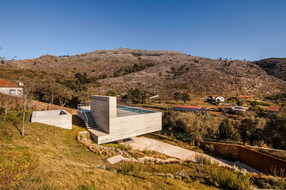 The house cantilevers off a steep site at the edge of a peaceful village