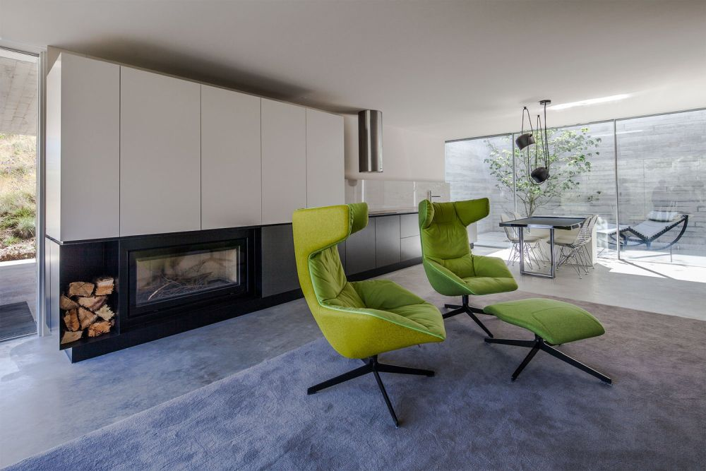 The open-space living room has a modern built-in fireplace and fresh green color accents